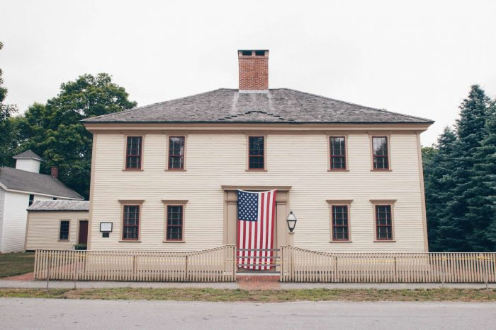 A New England House with an American Flag on the front