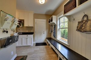 Mudroom at entryway of the home with benches and sink